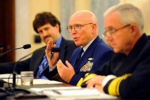 Three men in uniform talking at hearing