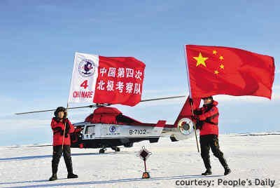 Two people with flags on the North Pole, helicopter in the back