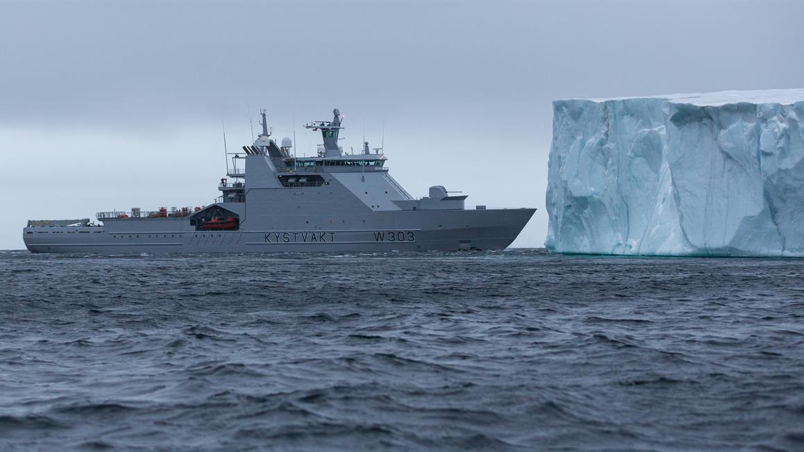Military vessel next to iceberg