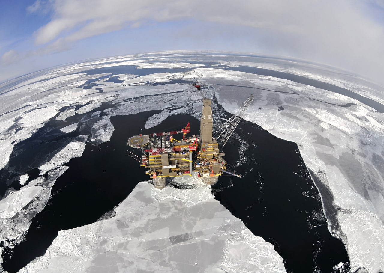 Arial shot of oil and gas platform surrounded by ice floes