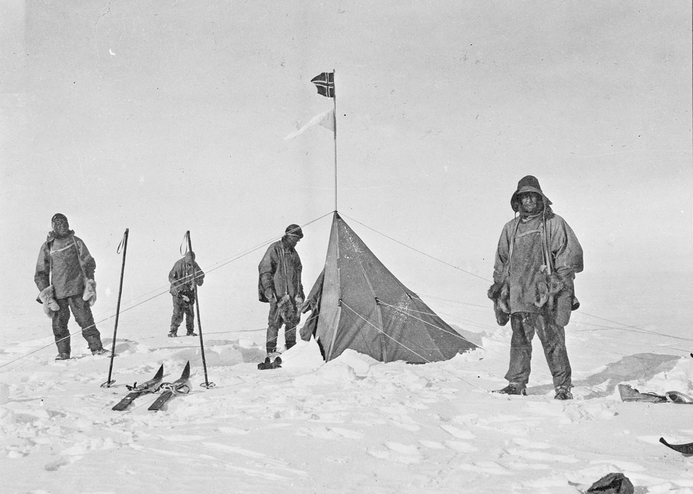 Black and white picture of men standing in front of tent at the South Pole