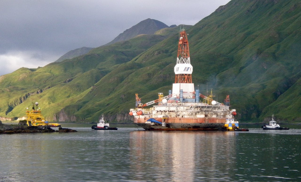 Oil drilling platform with mountains in background