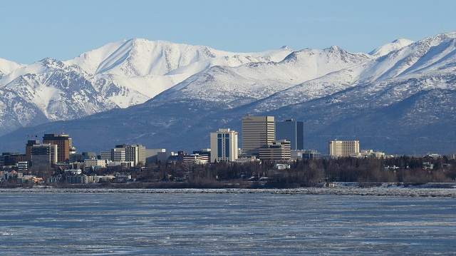 Tall buildings in downtown Anchorage with the Chugach Mountains in the background.