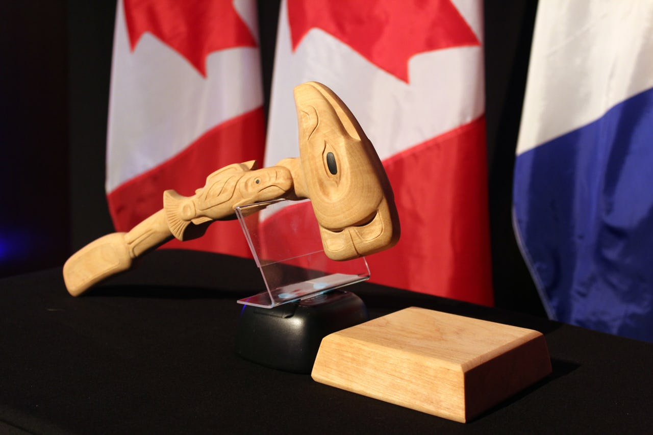 Gavel made of wood on table with flags as background