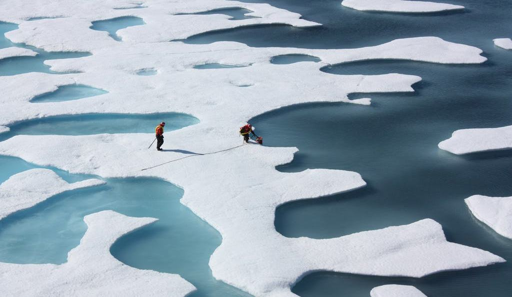 2 people standing on sea ice with many ponds surrounding them