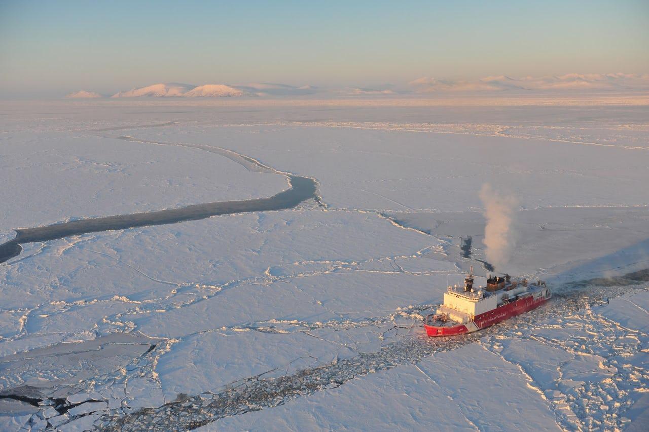 Vessel breaking through Arctic sea ice