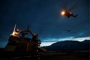Helicopter approaching vessel at night.