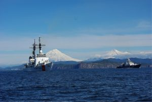 Two vessels on ocean with snowy mountains in the back