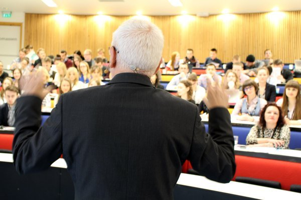 Man facing camera with his back talking to audience