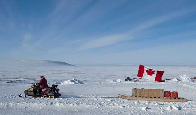 Man on snowmobile with Canadian flag