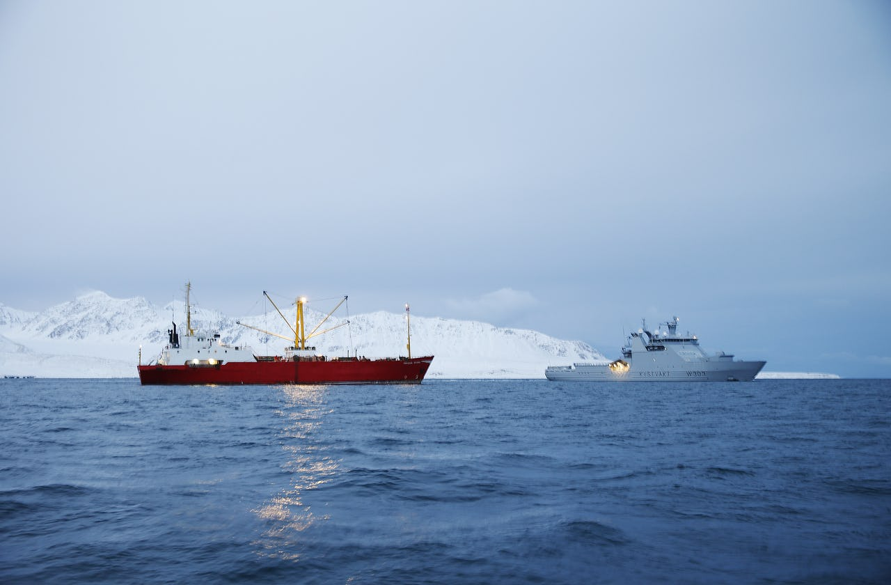 Two vessels on sea with snow mountain as background