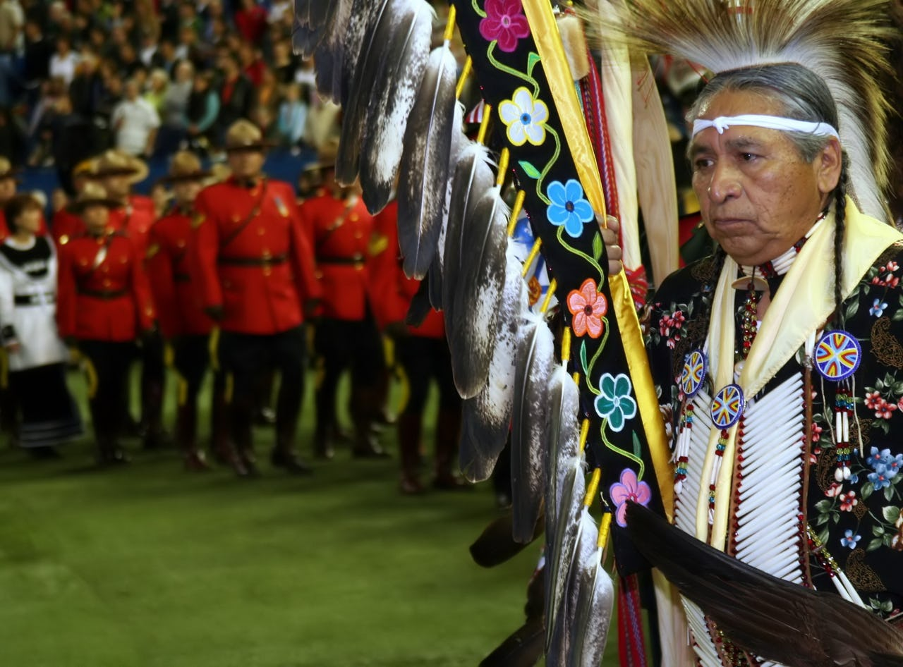 Old man holding indigenous flag