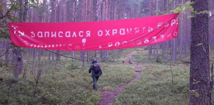 Person walking on forest path under big red banner