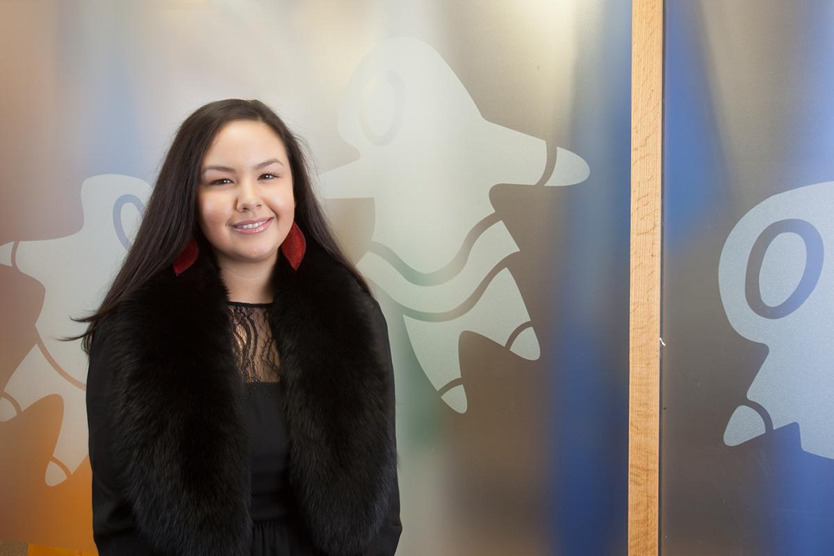 The president of the National Inuit Youth Council Maatalii Okali sitting in front of banner.