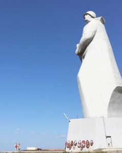 Big soldier statue with blue sky in the background.