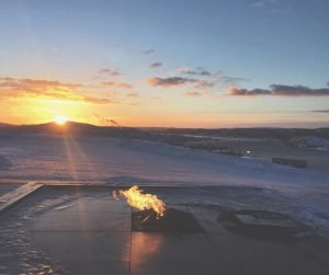 Sun coming over the horizon in icy landscape.