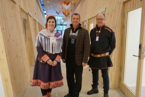 Three people standing in wooden hallway, two with traditional Sami clothes