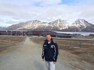 Man standing in front of buildings with snowy mountains in the background