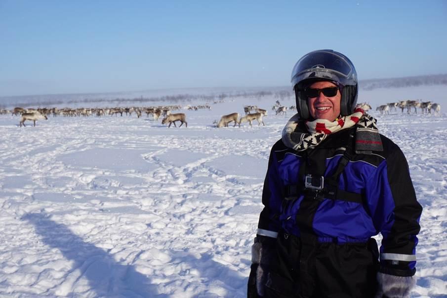 Man standing in front of reindeer herd in snowy landscape