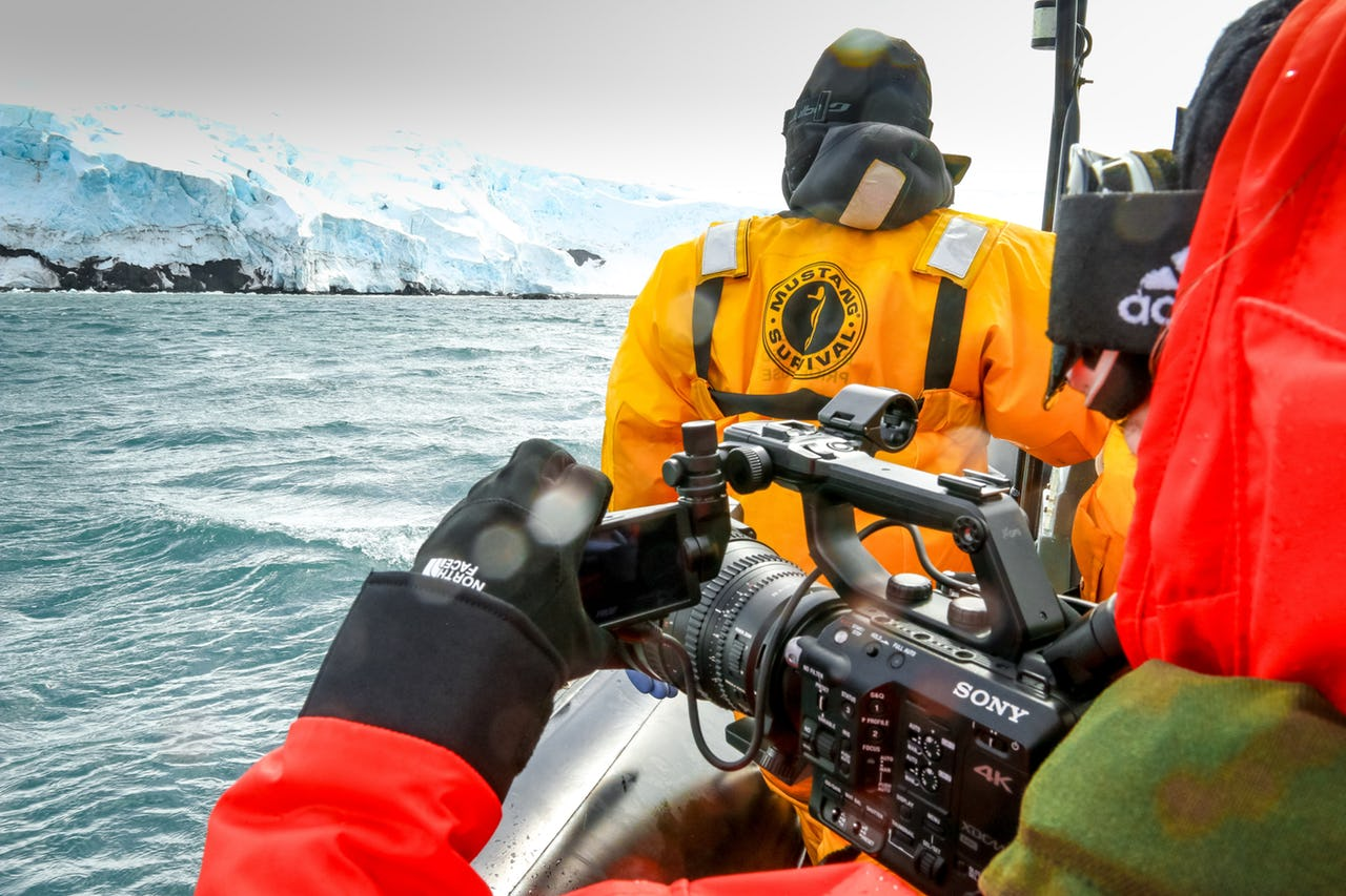 Person filming an iceberg with camera as part of the IMO delegation to Antarctica