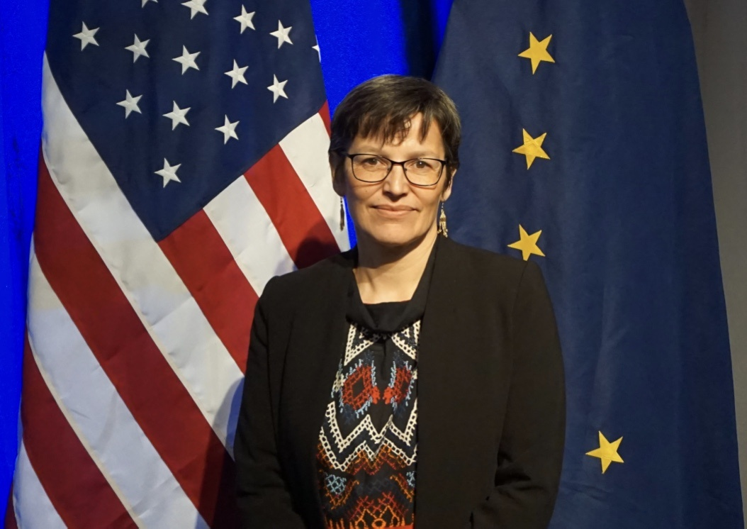 Greenland's Minister of Foreign Affairs, Suka K. Frederiksen, which is part of the Danish delegation to the Arctic Council stands in front of the Stars and Stripes and the Alaskan flag