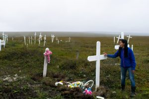 A woman in a cemetery next to a white grave cross