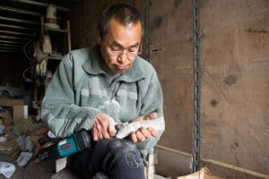 A man carving a sculpture out of a moose antler