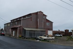 An old red store building with a rusty car in front of it
