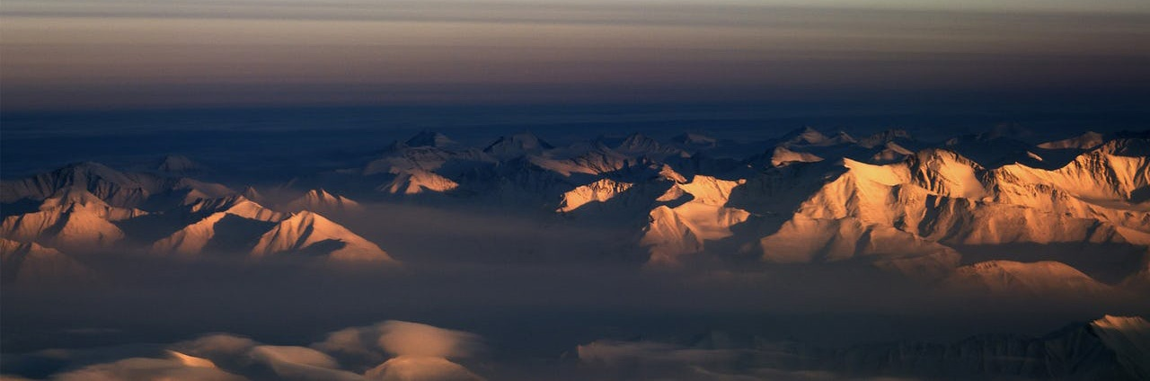 Aerial view of morning sun reflected off mountains in northeastern Greenland with the moon in the sky.