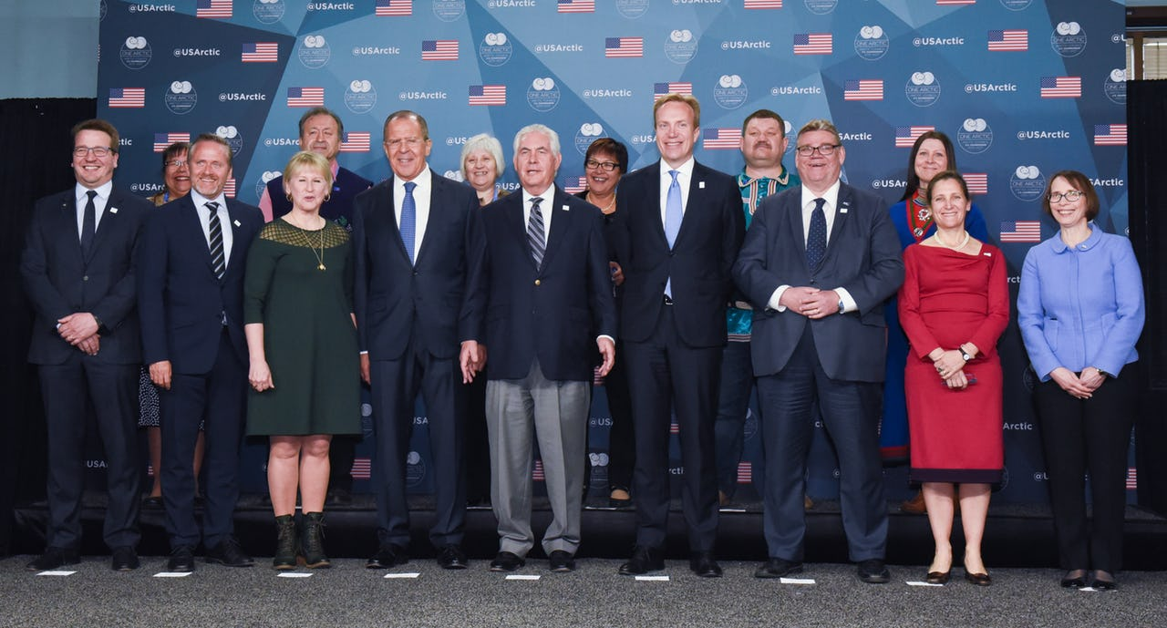 A group of men and women standing in front of a wall with US flags and Arctic Council logos.