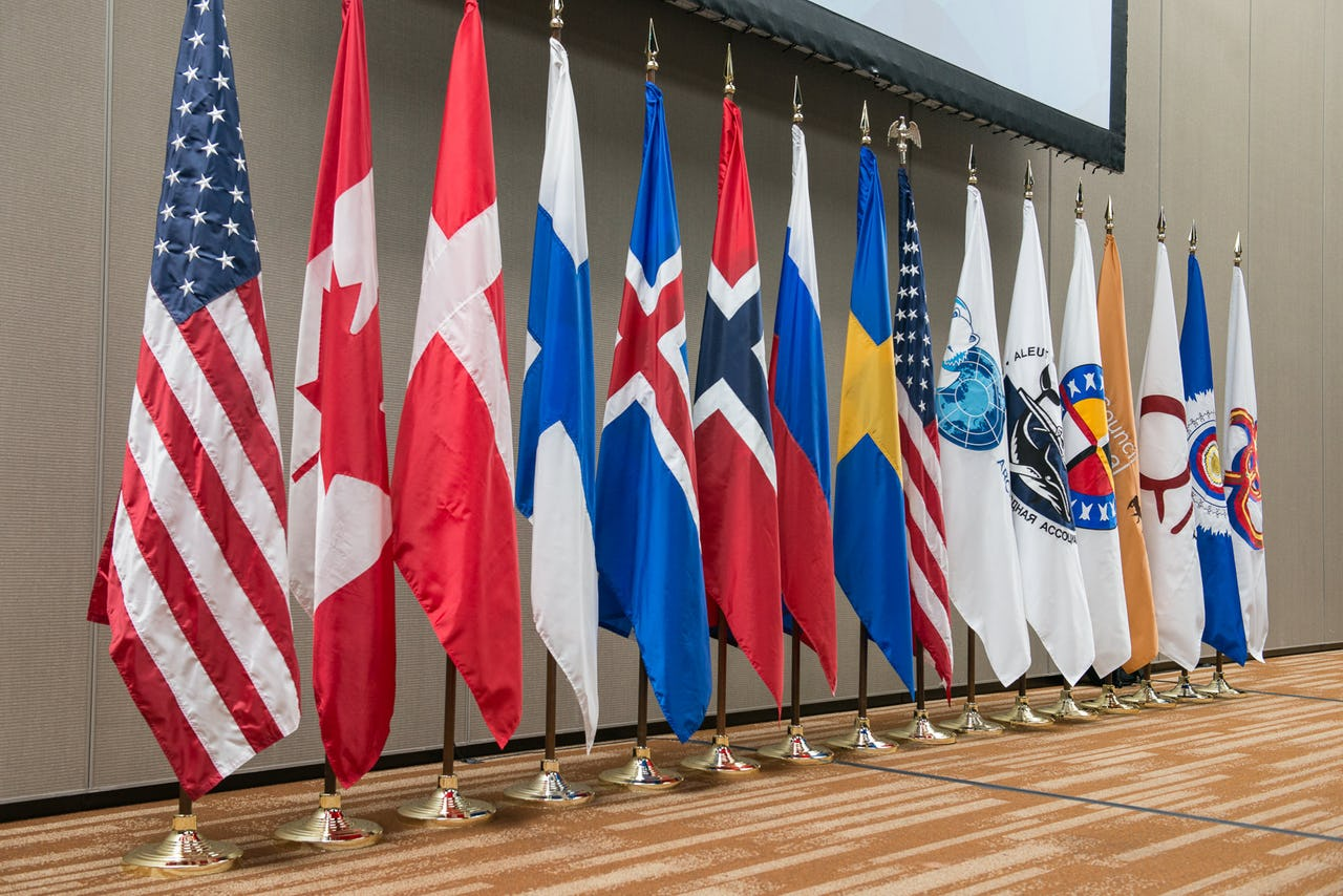 Sixteen flags standing against a wall, showing the flags of the eight Arctic Council Member States and six indigenous Permanent Participant organizations.