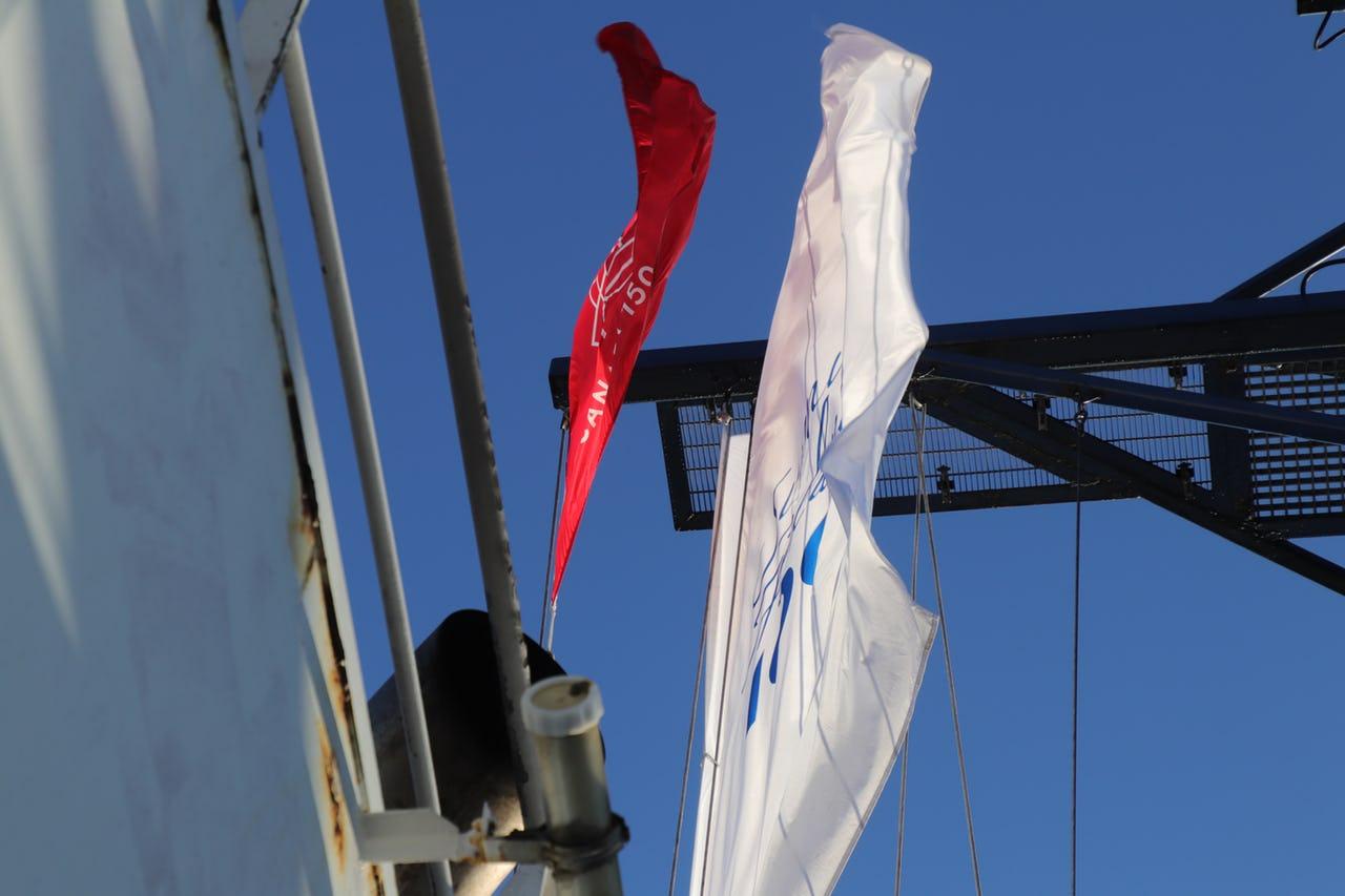 Flag flying on top a ship against blue sky.