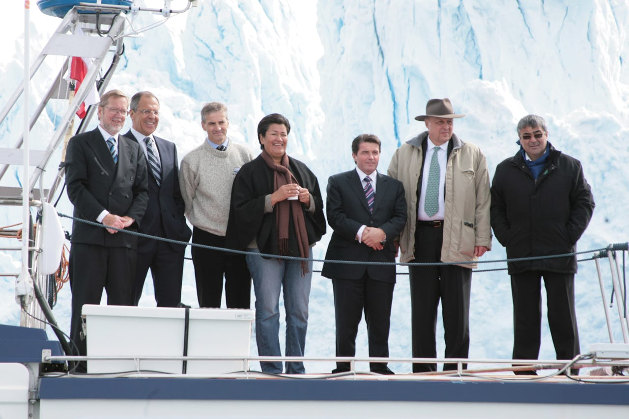 Seven people standing in front of an iceberg on a ship
