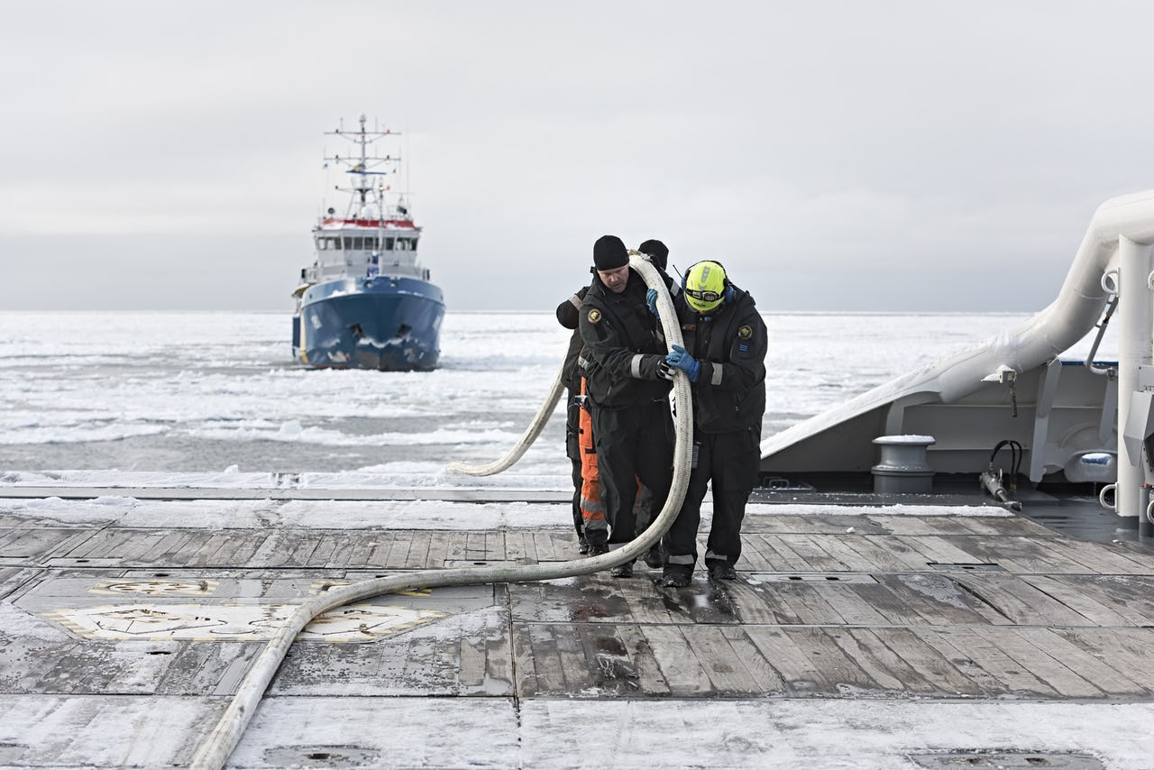 Three men carrying a hose on board a ship with icy waters and another ship in the background.