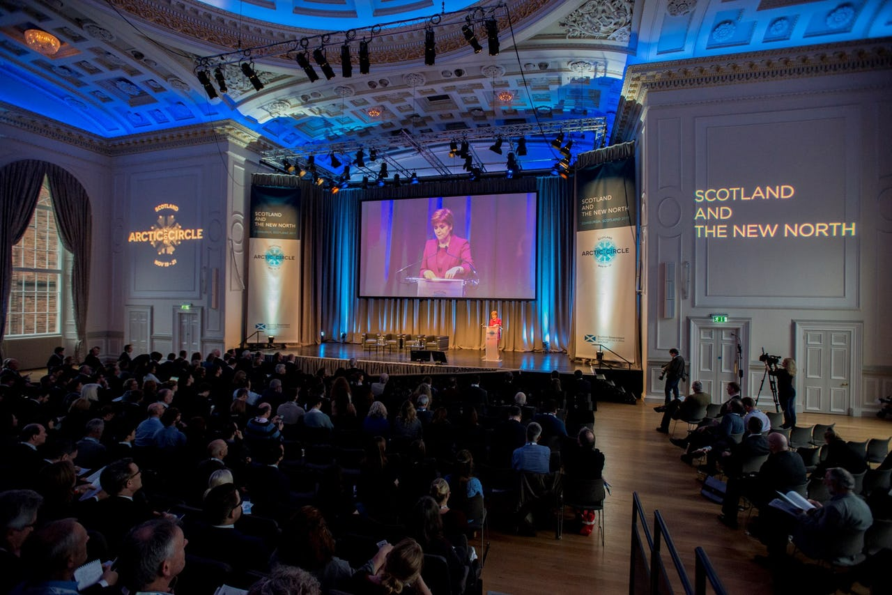 Crowd of people in a large conference hall in Scotland with a woman on a large screen in the background