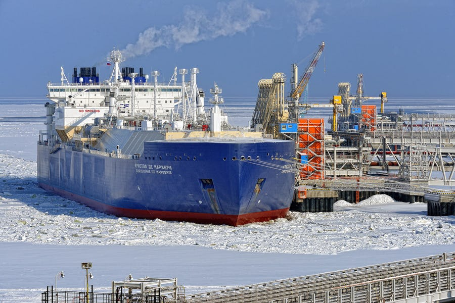 Big blue ship at a dock surrounded by ice-covered waters