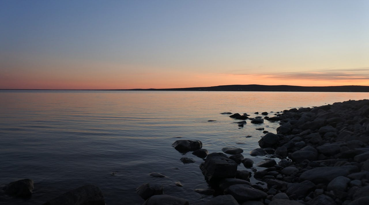 Sunset on water with rocks and mountain